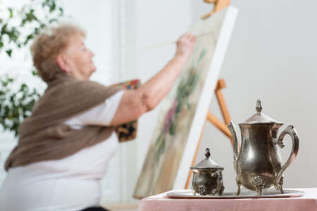 Active senior woman using easel during painting