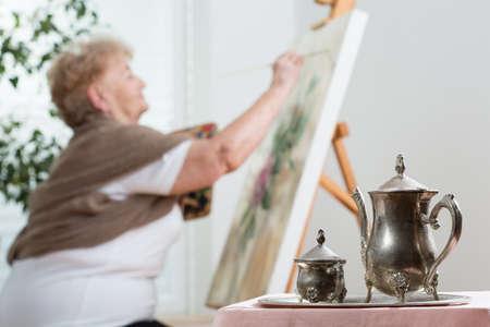 Aktive ältere Frau mit Staffelei beim Lackieren Standard-Bild - 35821813