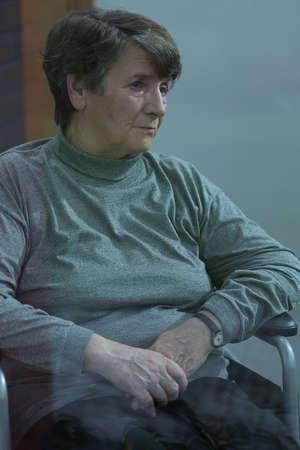 melancholijny: Vertical view of older melancholic woman sitting alone