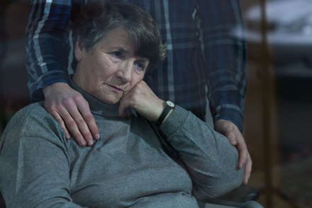 Senior depressed woman and her supportive son photo
