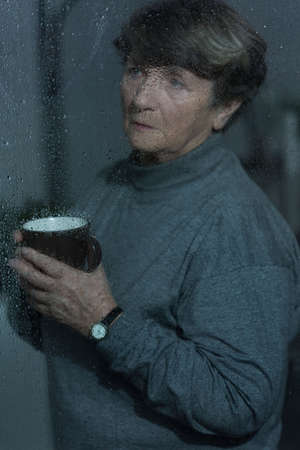 grieved: Picture of older grieved woman looking outside