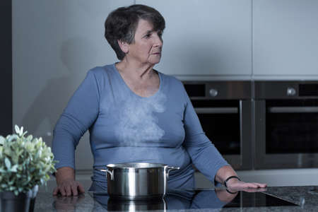 spiritless: Aged sad woman cooking in the kitchen