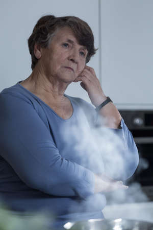 sorrowful: Senior sorrowful woman deep in thought in the kitchen