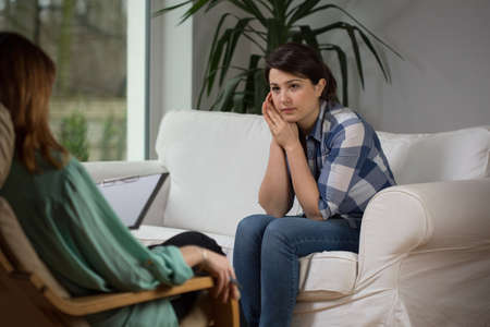 Young woman talking with psychologist about her problems Stock Photo