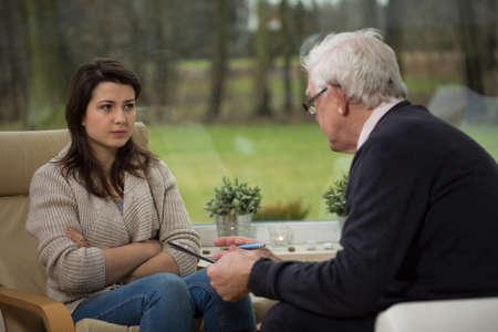 Despair worried girl talking with elder psychiatrist