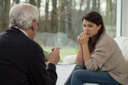 psychotherapy: Sad teenage girl talking with her psychologist Stock Photo