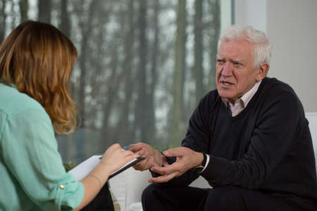 Elderly patient talking with psychotherapist about his troubles Stockfoto