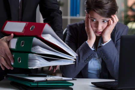 stressed business woman: Unfair chief giving assistant a lot of work Stock Photo