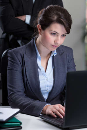 Working female employee being controlled by boss photo