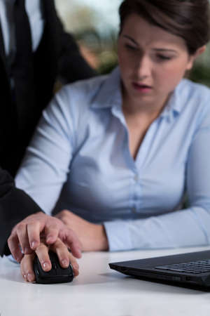 violence in the workplace: Young afraid secretary being bullied by boss Stock Photo