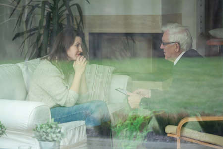 diagnosing: Elder therapist consulting young patient at home Stock Photo