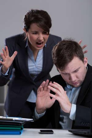 acoso laboral: Jefe gritando a su ayudante en corporación Foto de archivo