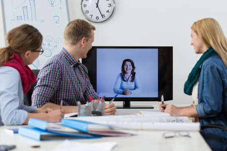office meeting: Office workers during business conference on the tv Stock Photo