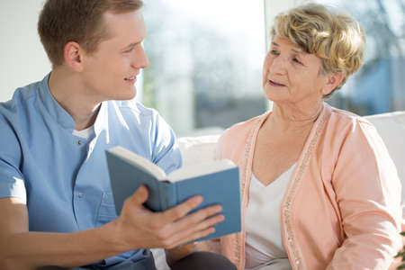 Young male nurse spending his free time with elderly woman Stock Photo