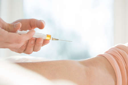 doctor giving glass: Close-up of male nurse doing the injection Stock Photo
