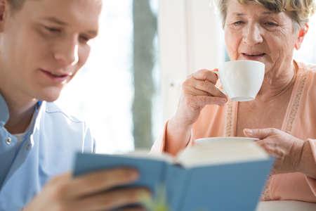 dos personas platicando: Feliz del gasto de mujer mayor agradable tarde con su cuidador masculino Foto de archivo
