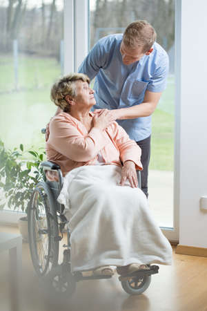 color therapist: Aged disabled woman on wheelchair and her thoughtful male nurse Stock Photo
