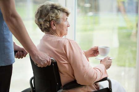 persona en silla de ruedas: Una más vieja mujer triste en silla de ruedas mirando por la ventana Foto de archivo