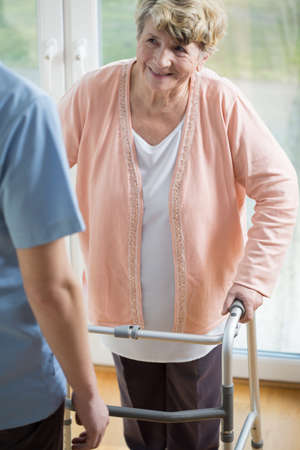 walker: Senior disabled woman with walker talking with her caregiver Stock Photo