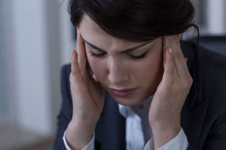 throbbing: Close-up of young businesswoman with migraine