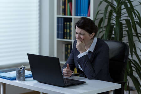 sedentary: Young tired businesswoman sitting after hours in office