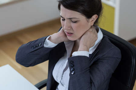 ache: Young sitting woman in office with pain of spinal column