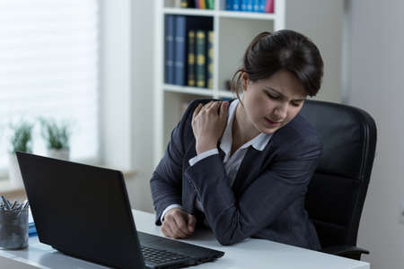 overloading: Young overworked businesswoman with pain in shoulder