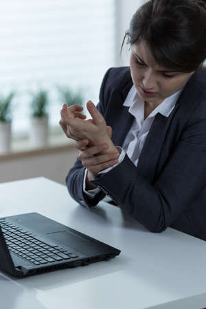 wrist pain: Woman with wrist pain after typing on computer
