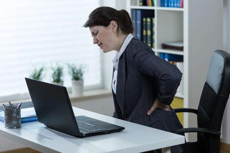 ひどい腰痛を持って座って仕事を持つ若い女性
