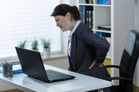 Young woman with sitting job having terrible backache photo