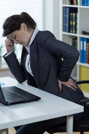 sedentario: Mujer con el estilo de vida sedentario que tiene dolor en la columna lumbar