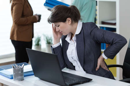 overloading: Young pretty busy woman suffering from pain Stock Photo