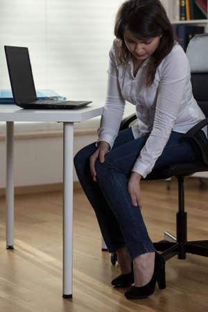 sedentario: Secretaria bonita joven con tacones altos que tiene dolor en las piernas Foto de archivo