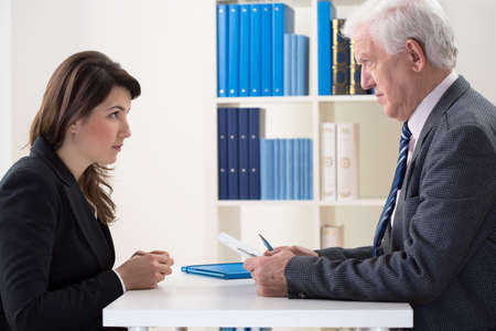 company employee: Young pretty afraid woman on her job interview Stock Photo
