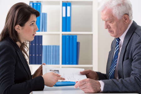 first job: Young attractive woman giving to the interviewer her curriculum vitae Stock Photo