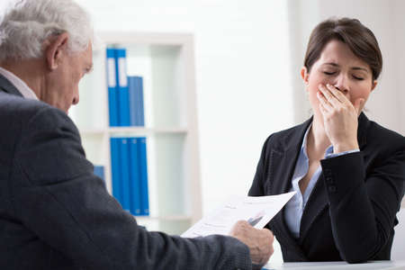 unprofessional: Young female interviewer yawning on recruitment meeting Stock Photo