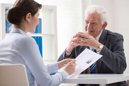 Elder man answering the questions on job interview Banco de Imagens