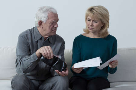 penniless: Worried aged marriage checking wallet Stock Photo
