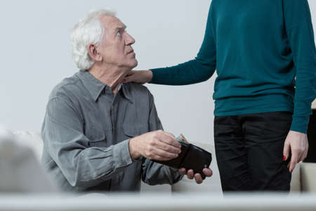 penniless: Elderly worried man and his supportive wife