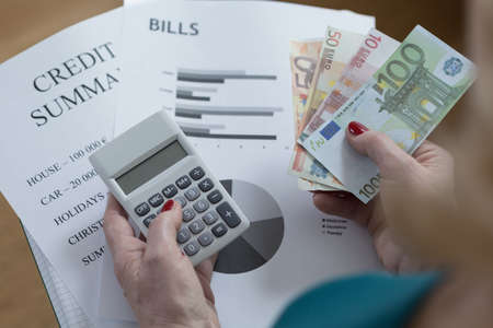 summary: Close-up of credit summary and money counting Stock Photo