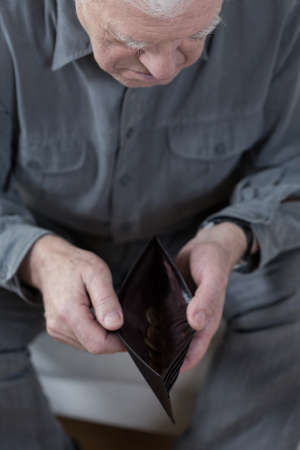impoverished: Vertical view of impoverished man looking to empty wallet Stock Photo