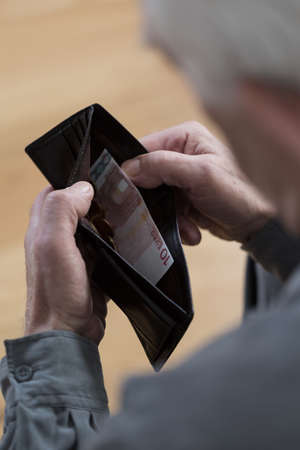 impoverished: Close-up of elderly mans last banknote in wallet