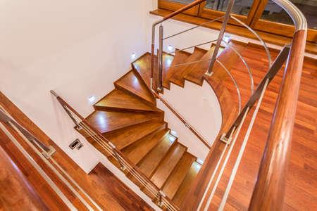 subiendo escaleras: Primer plano de sinuosas escaleras de madera en la mansi�n de lujo