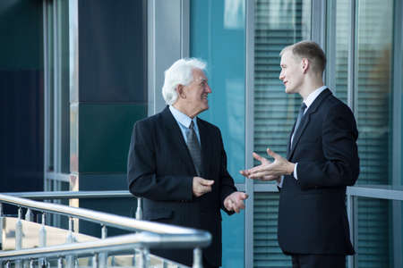 workmate: Senior chief and his employee talking out of business building Stock Photo