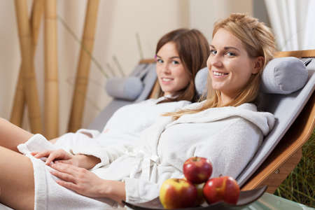 chair massage: Lady friends sitting on deck chair in spa