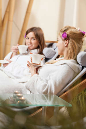 Lady friends drinking tea at spa room