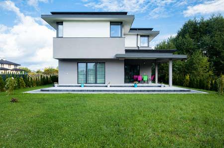 大きな庭のある新しいモダンな家の写真