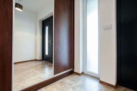 closet door: Big wooden closet with mirror on the door