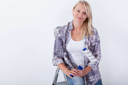 priming paint: Young woman with paint roller sitting on ladder