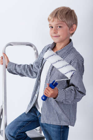 redecorate: Child holding paint roller standing on ladder Stock Photo